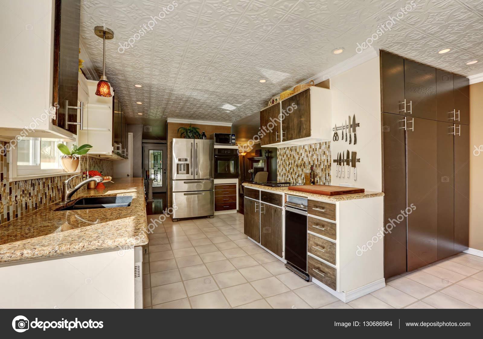 Cocina comedor en tonos marrones con combinación de almacenamiento ...