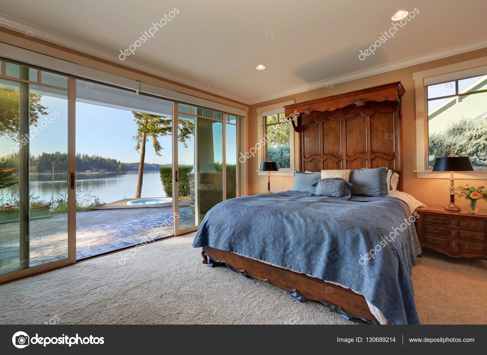 Grote slaapkamer. Bed met hoge houten gesneden voorbord — Stockfoto ...