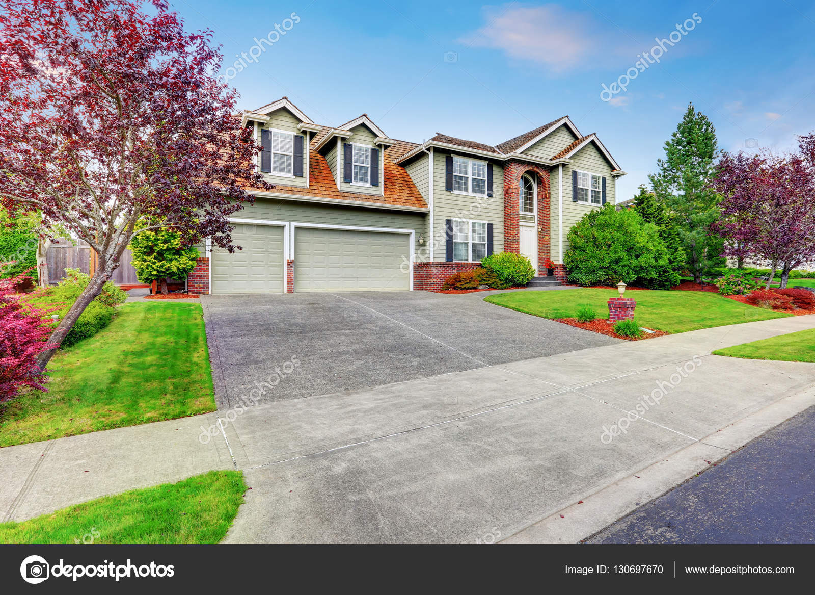 luxury house exterior with red brick trim and arched entry stock photo 130697670