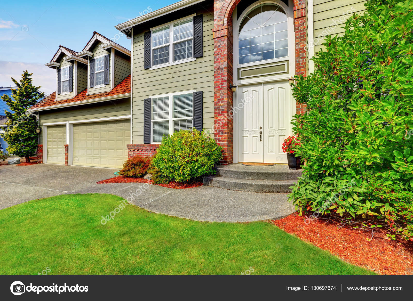 luxury house exterior with red brick trim and arched entry stock photo 130697674