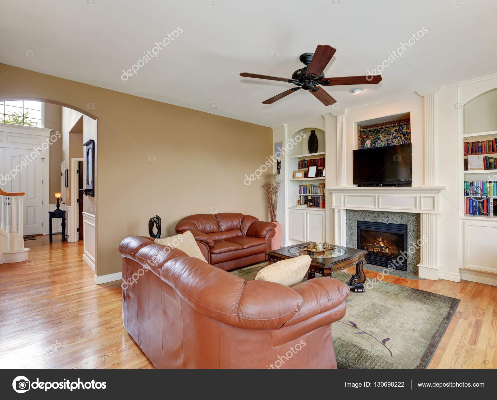 Gemütliche Familienzimmer mit braunem Leder-Sofas und Kamin ...