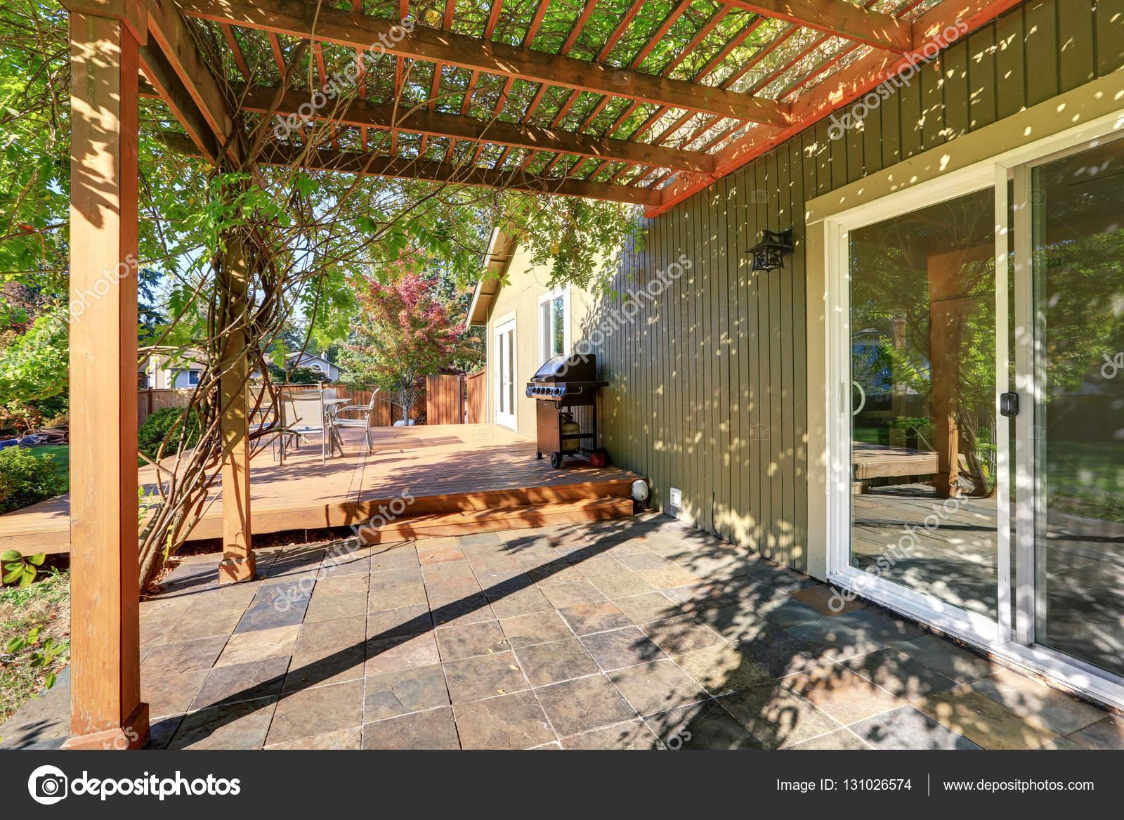 Achtertuin met pergola tegelvloer en houten staking dek