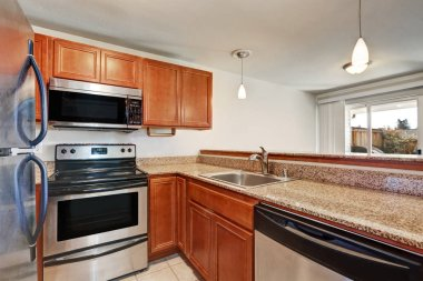 Small kitchen features shaker cabinets with granite countertop.