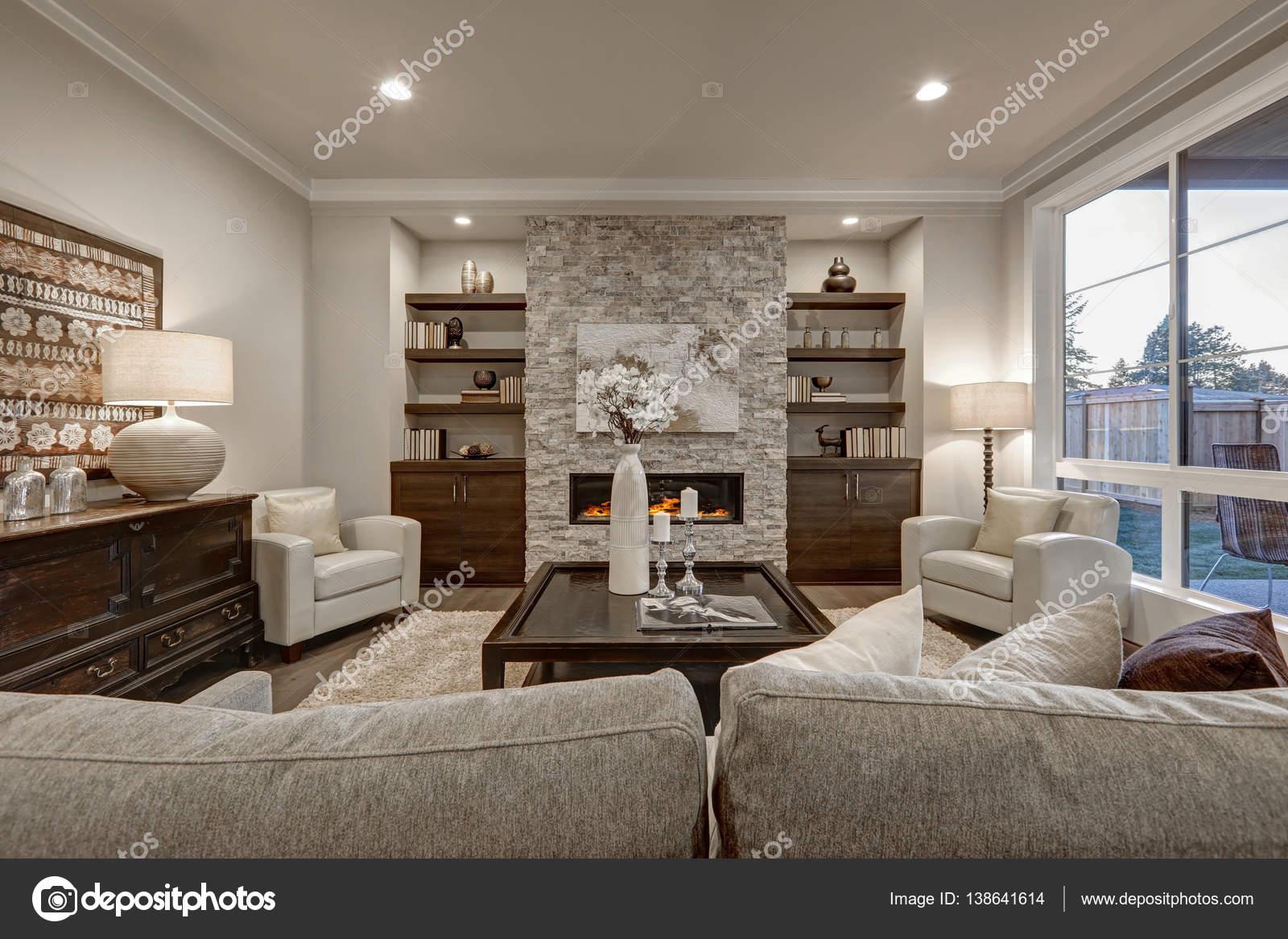 woonkamer interieur in grijs en bruin kleuren functies stenen open haard met ingebouwde planken en kasten grote donker gekleurd cocktail tabel atop beige