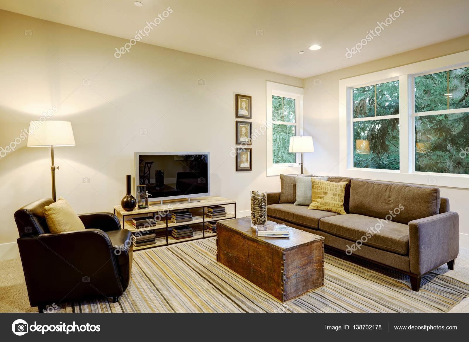 familiekamer interieur met grijze bank en boomstam salontafel stockfoto