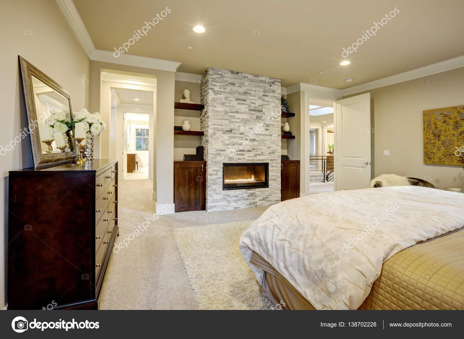 beige y marrn dormitorio cuenta con cama de reina frente a la hermosa chimenea de piedra enmarcado por estantes noroeste nos u foto de irianaw