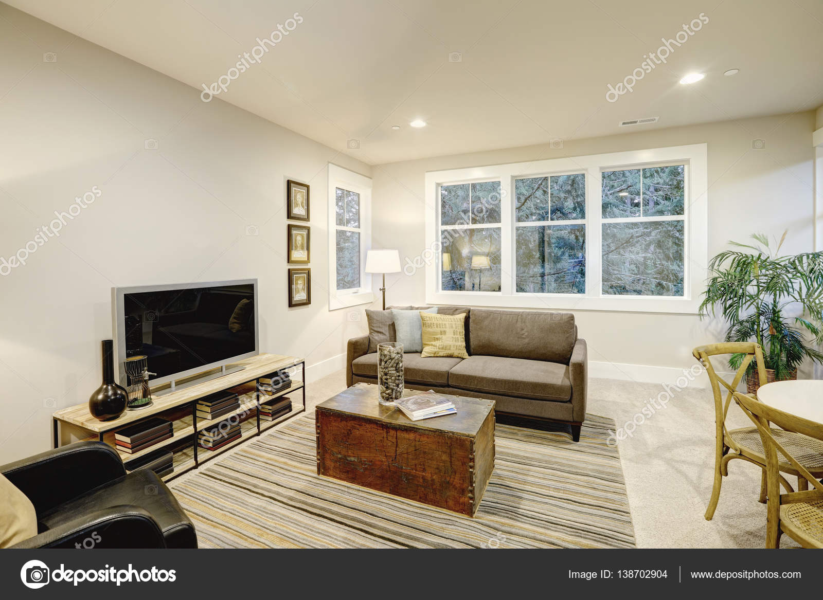 familiekamer interieur met grijze bank geconfronteerd met een zwart lederen fauteuil tegenover een boomstam salontafel bovenop een grijs en bruin gestreepte