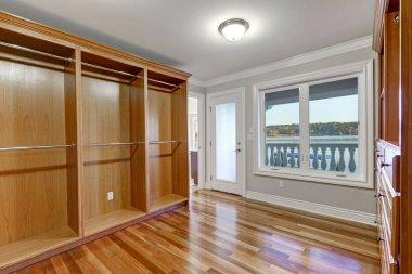 Empty walk in closet with hardwood floor and door to balcony