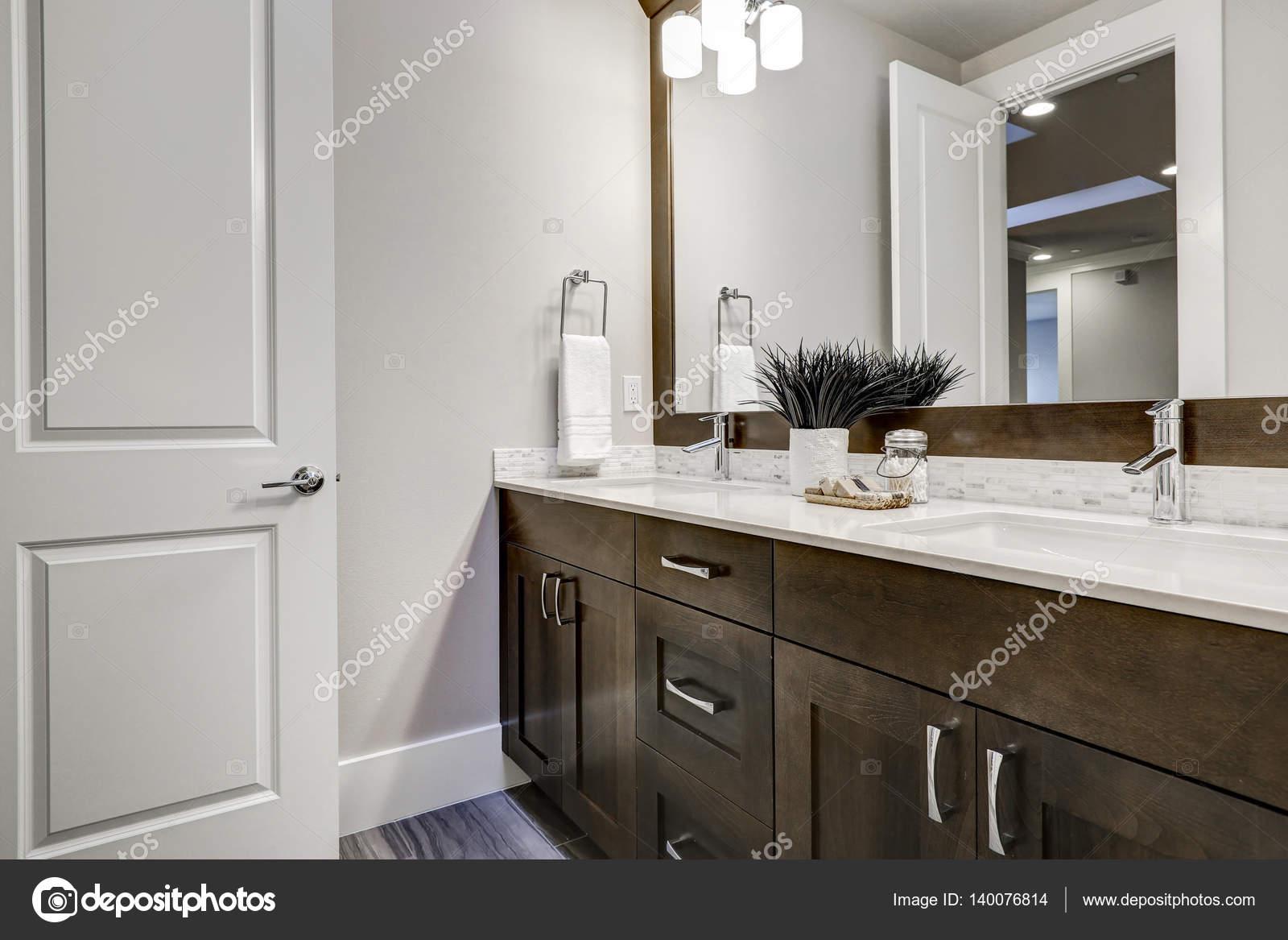 Witte en bruine badkamer beschikt over een hoekje gevuld met dubbele ...