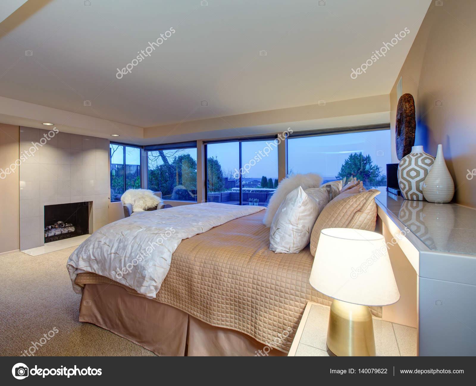 Härligt sovrum design med öppen spis och utgång till altan ...