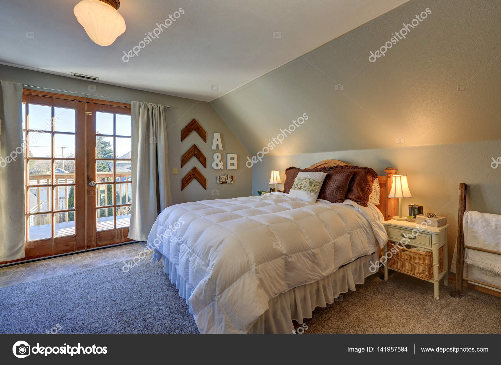 Ruhigen Schlafzimmer Im Obergeschoss Mit Dachschräge Und Doppelten  Glastüren, Schöne Terrasse, Mit Weißen Bett Garniert Mit Braunen Kissen  Ausgestattet.