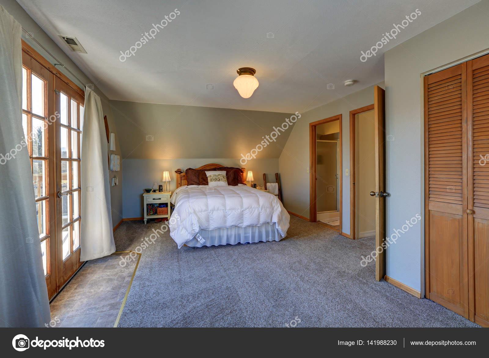 Rustige slaapkamer met schuin plafond en deuren naar mooie dek ...