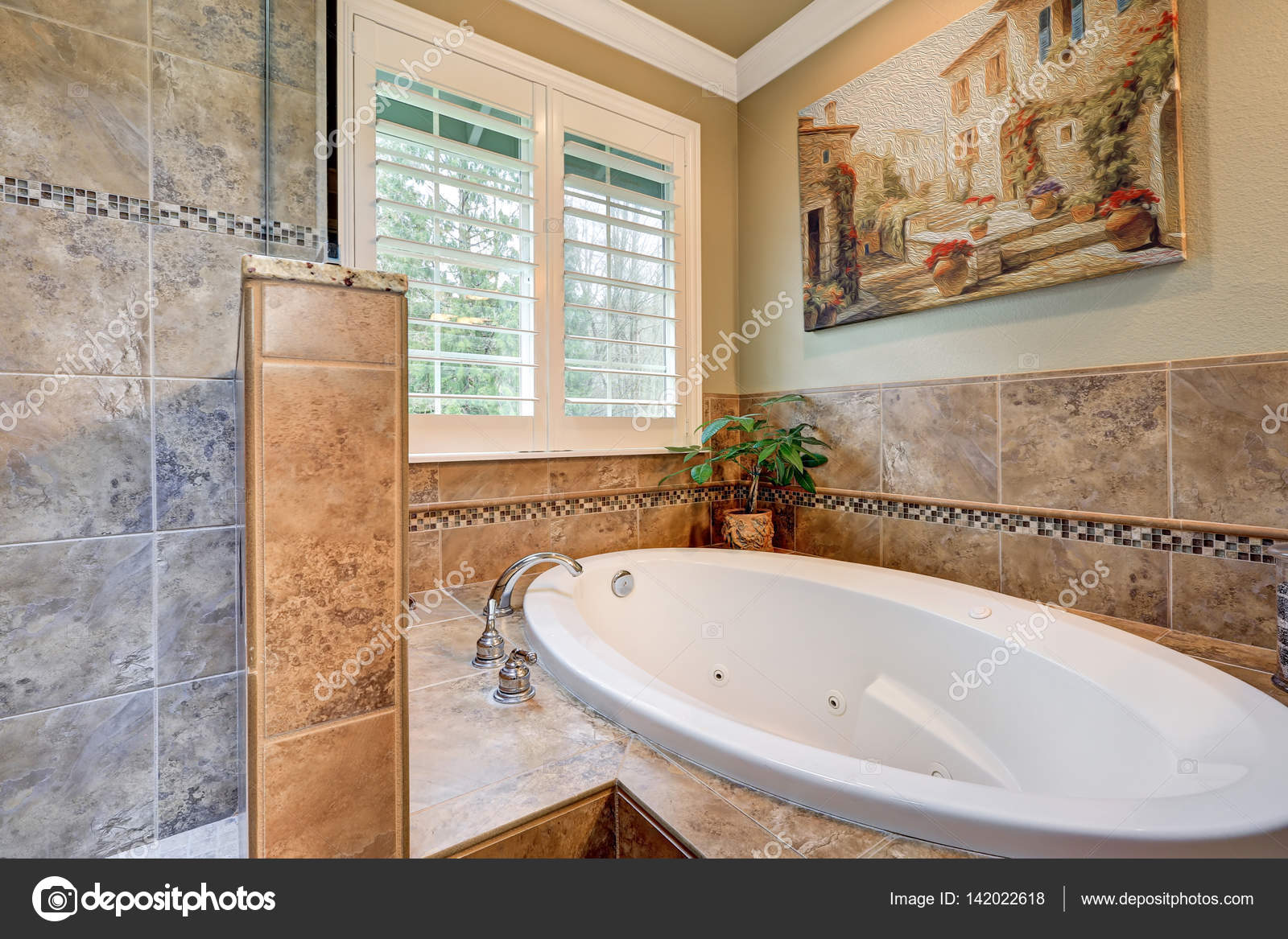 Lovely bathroom boasts jetted tub with a brown mosaic tile surround ...