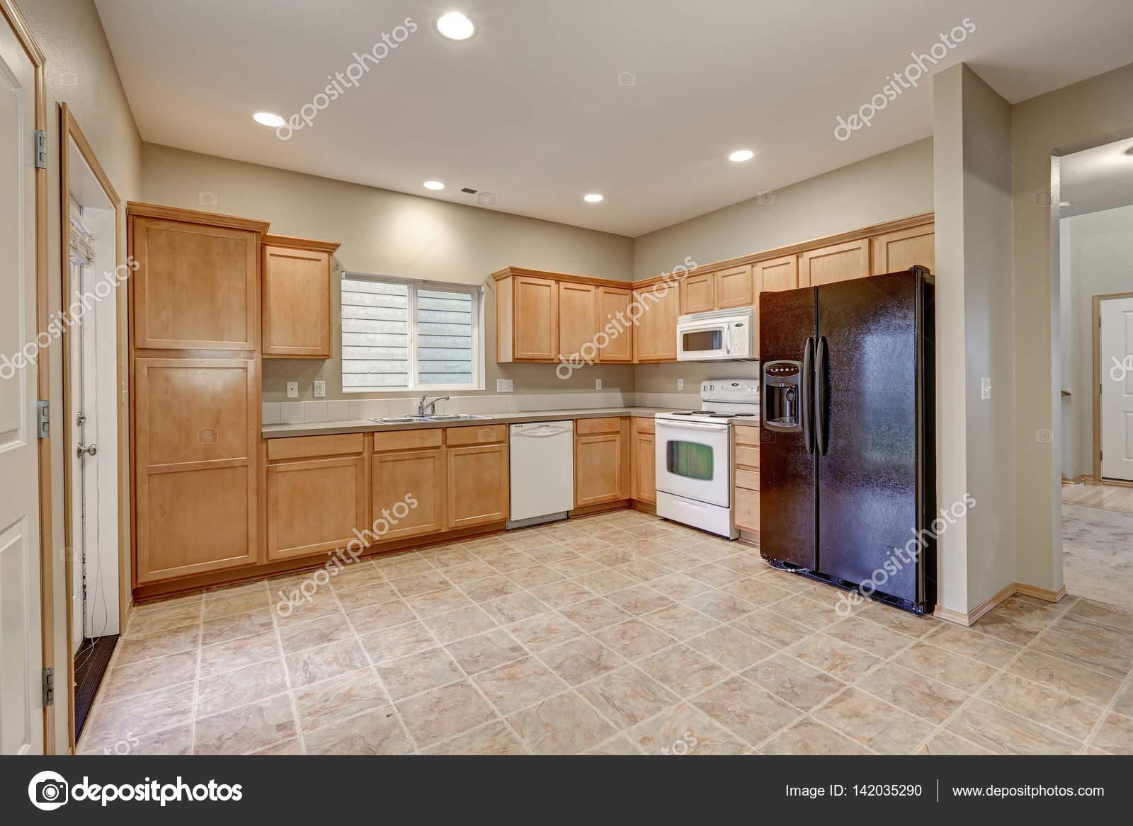 Helle Und Luftige Küche Zimmer Mit Frisch Gestrichenen Wänden In Beige  Farbe, Leichte Holz Schränke Und Schwarze Kühlschrank Auf Fliesenboden.