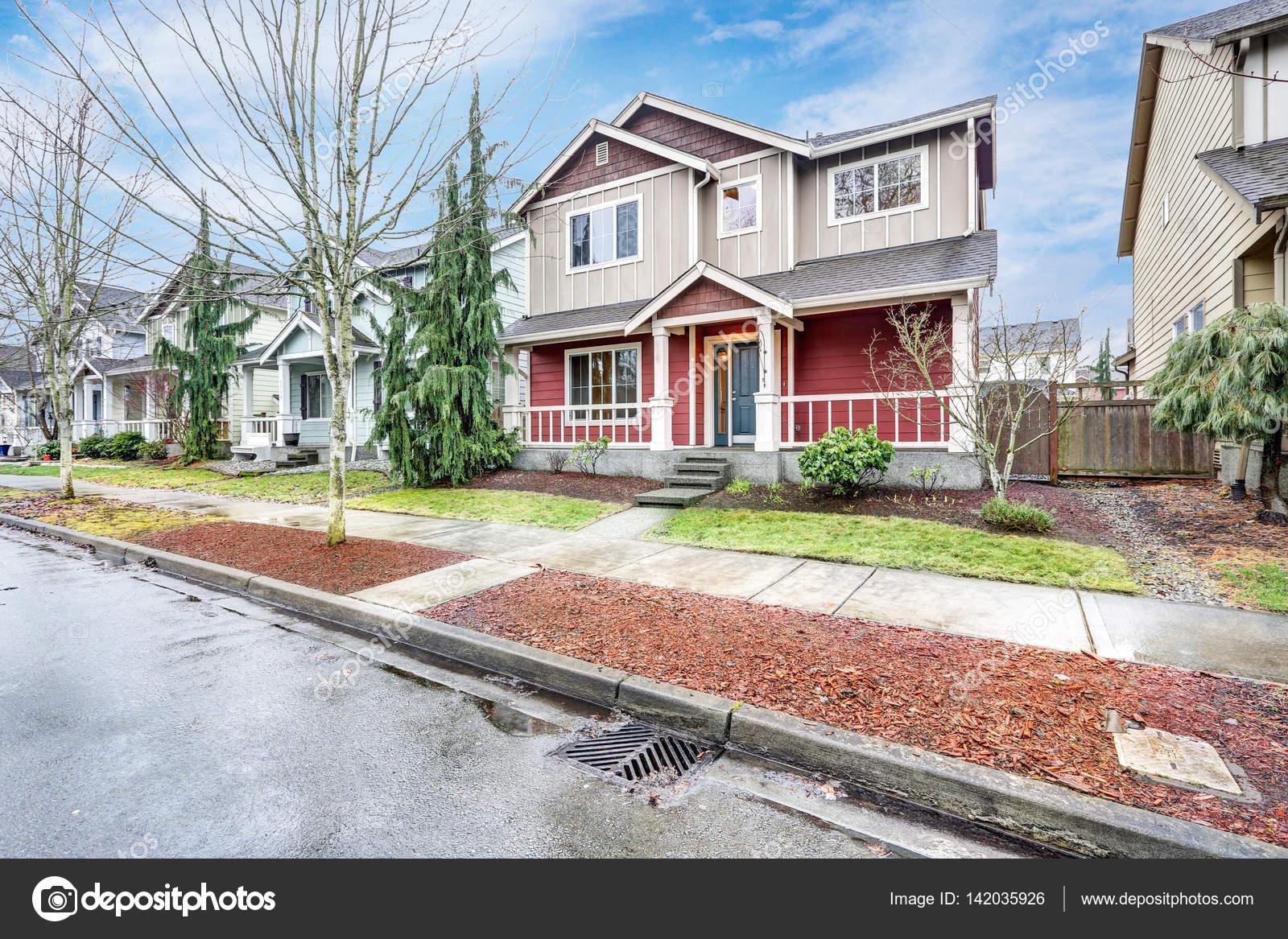 Hedendaagse rood en grijs home exterieur met overdekt terras