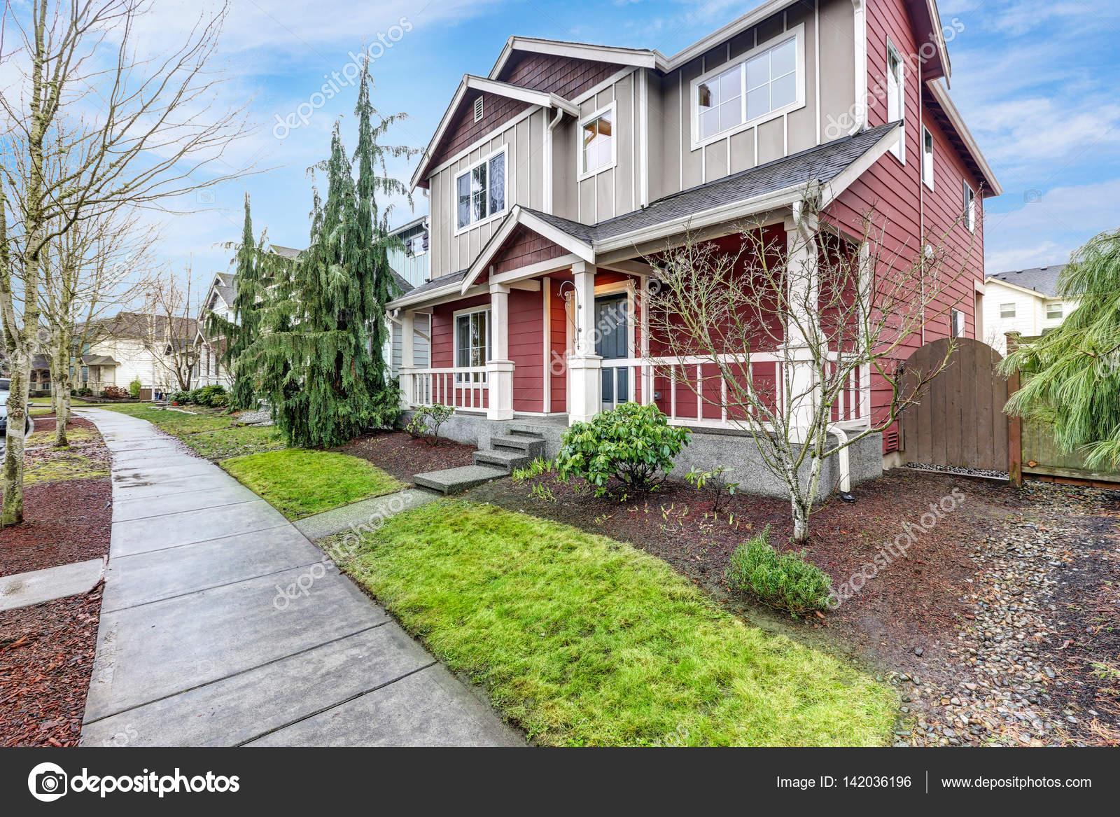 Zeitgenössische rot und grau Haus außen mit überdachten Veranda ...
