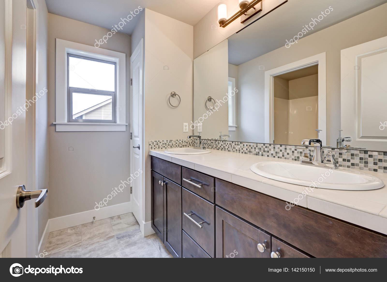 Nieuw interieur van het lichte badkamer met dubbele wastafel donker ...