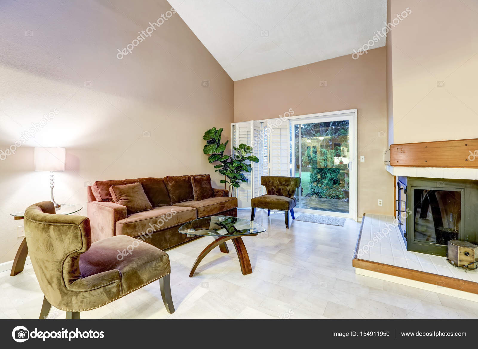 Family Room In Brown Tones With High Vaulted Ceiling Over Comfortable Velvet Sofa Two Tufted Chairs And Glass Coffee Table Facing Corner Fireplace