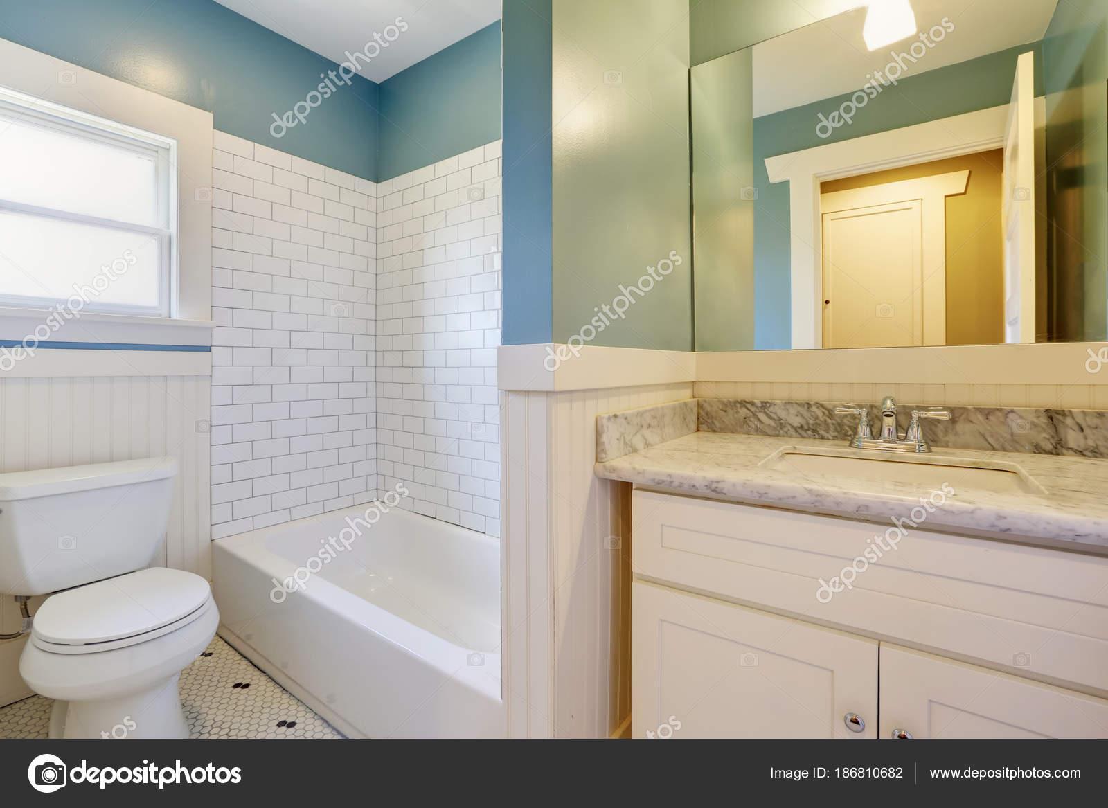 Bagno bianco e blu vengono visualizzati con ripiano in marmo
