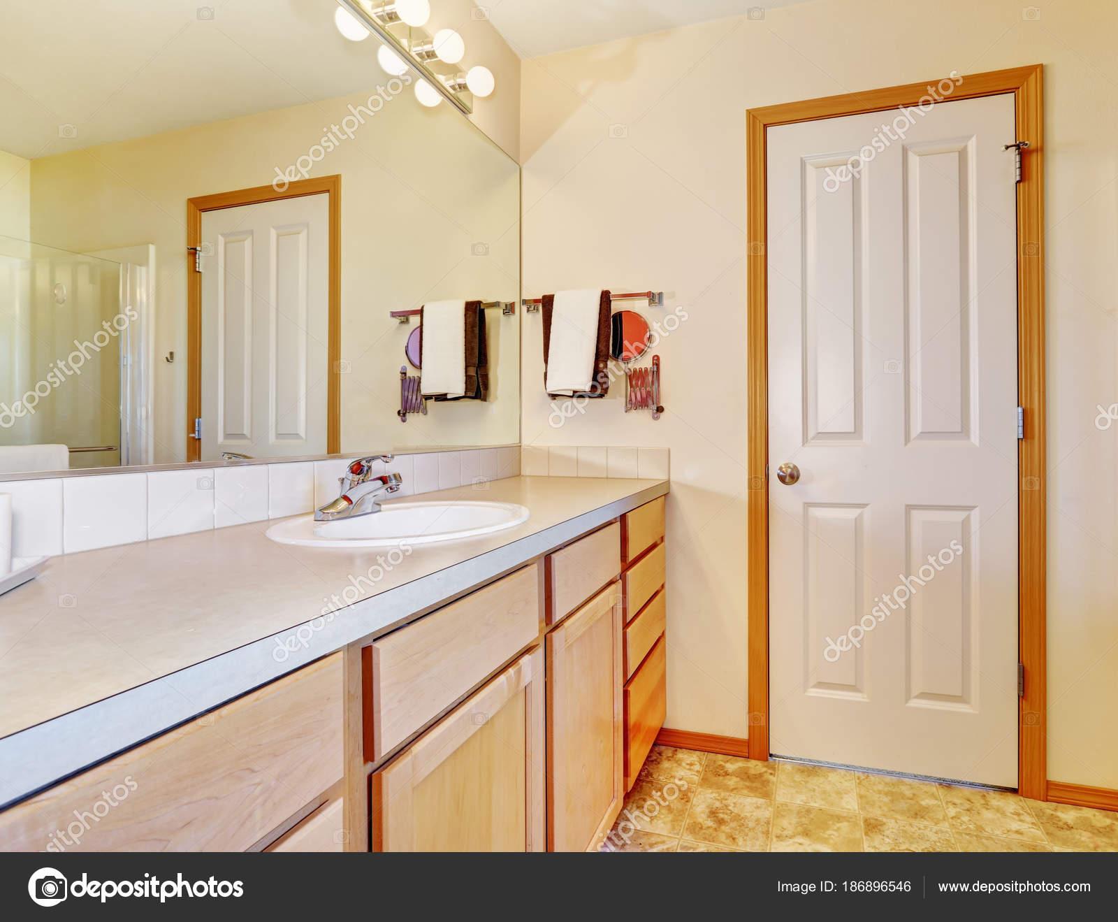 Salle de bain beige chaud avec armoires en bois clair — Photographie ...