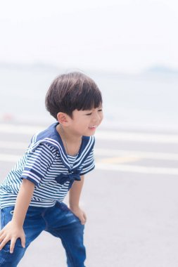 Portrait of young sailor boy with the sea.