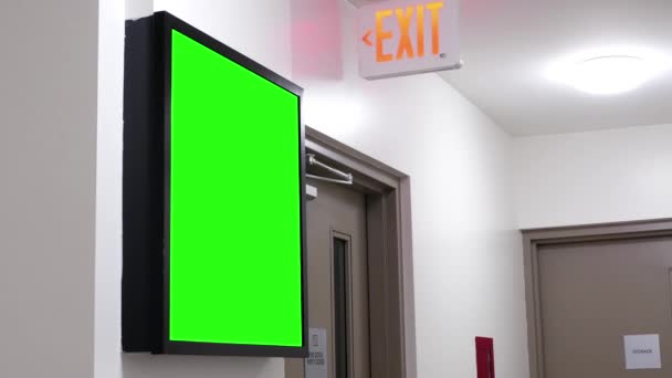 Green billboard for your ad beside exit sign for stairway