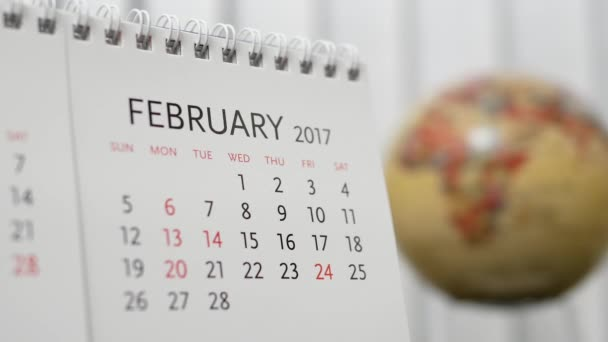 Motion of February 2017 calendar with blur earth globe turning background