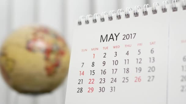 Motion of May 2017 calendar with blur earth globe turning background