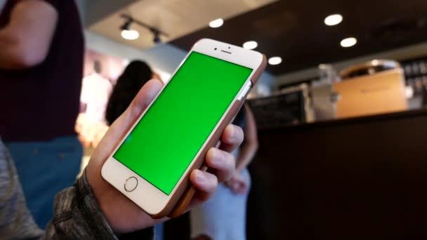 Ruce drží zelená obrazovka iphone uvnitř kavárna Starbucks