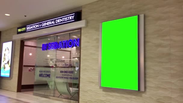 Green billboard for your ad on wall beside dentistry store inside Coquitlam shopping mall