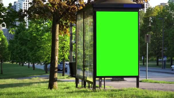 Green billboard for your ad at bus station with people crossing street