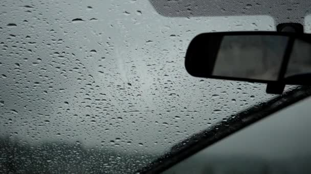 Slow motion of rainy day view during car windshield wipers rain drops sliding down
