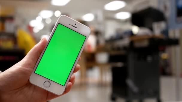 Pohyb ženy držící zelený displej mobilního telefonu na pohovce