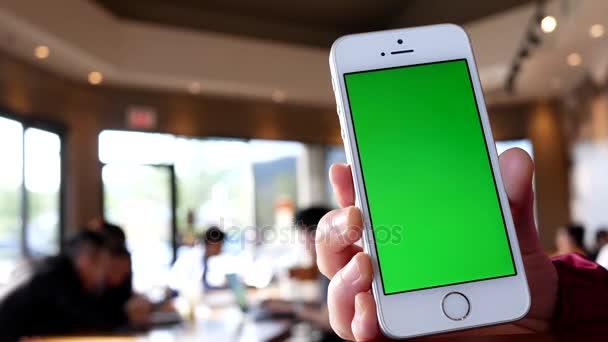 Ruka držící zelená obrazovka a na telefonu uvnitř kavárna Starbucks