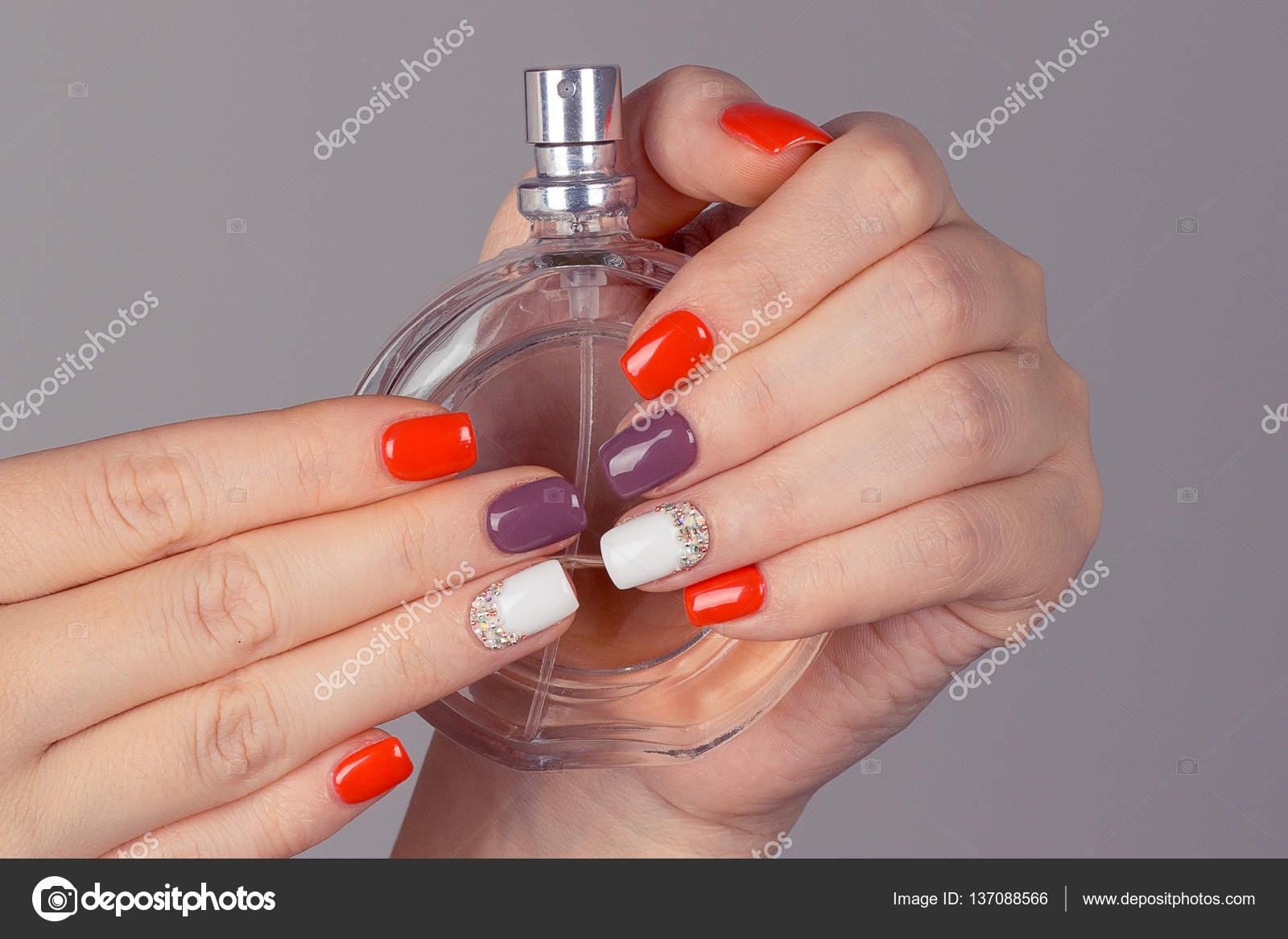 Closeup Nagel poliert bunte Nägel Hand, die Parfüm-Flasche ...