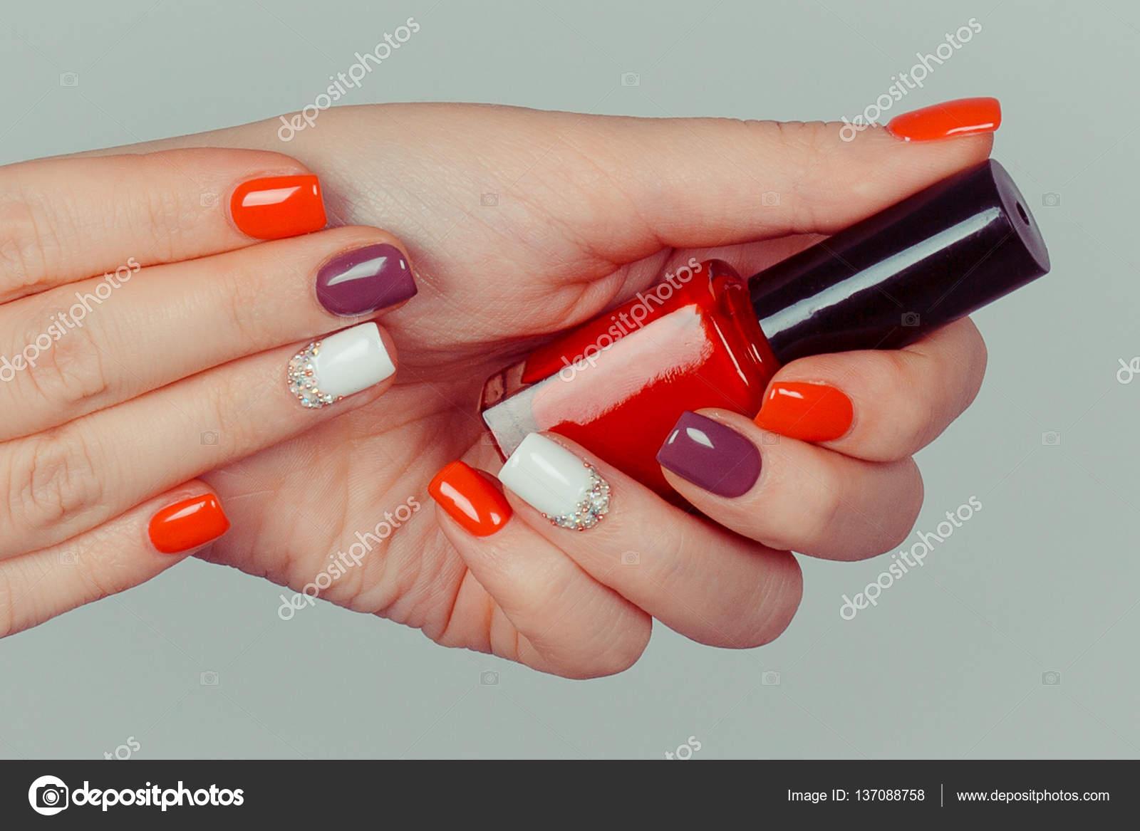 Manos con multi color rojo blanco marrón manicura y esmalte de uñas ...