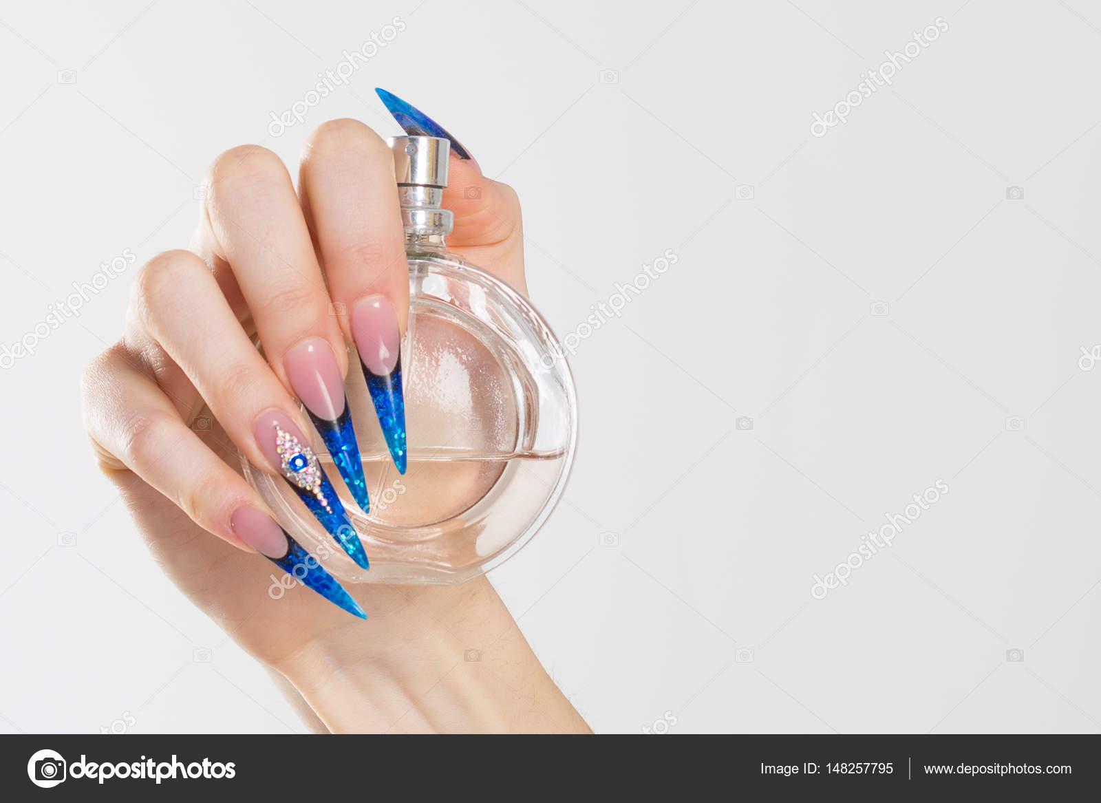 Closeup aguja azul pulido de uñas las uñas con cristales, mano ...