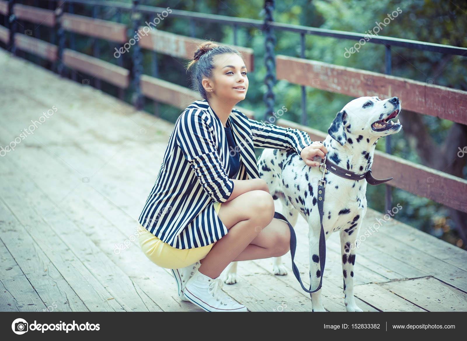 Chica guapa mujer en el puente de celebración de su perro que ladra ...