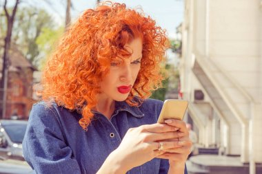 What??? Unhappy frustrated angry woman with red curly hair looking to mobile phone, reading something, standing outside with city background. Negative human emotions face expression feelings.