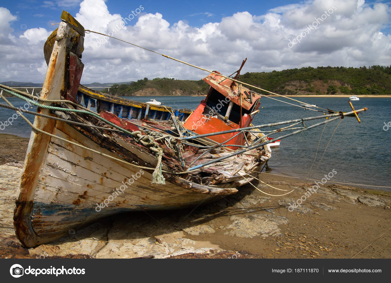 Old broken fishing boat wrecked against the river stock photo frontal view of an old fishing boat turned on a side wrecked and rotting on a rocky bank by the mira river bank bright blue clouded sky publicscrutiny Image collections