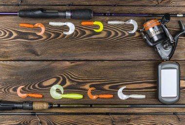 Fishing tackle - fishing spinning, fishing line, hooks, navigator and reel on wooden background