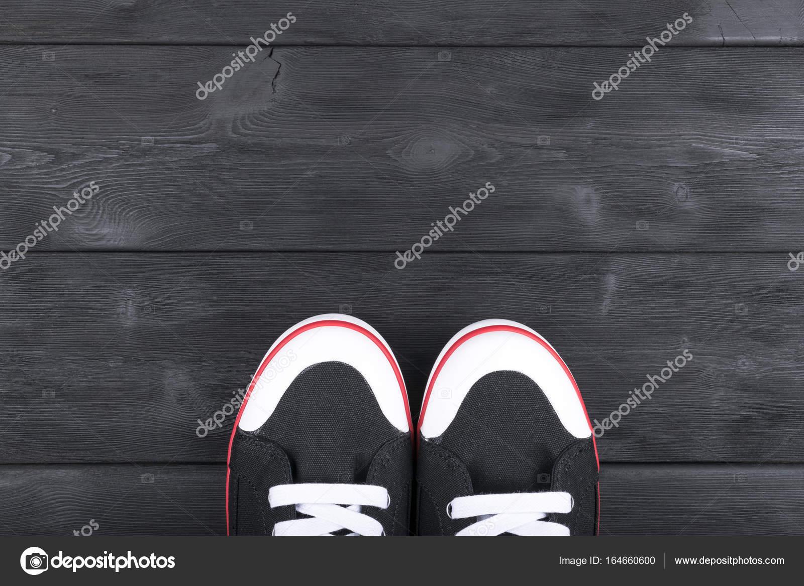 Bovenaanzicht van zwart wit schoenen op zwarte houten vloer
