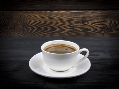 Overhead view of a freshly brewed mug of espresso coffee on rustic wooden background with woodgrain texture. Coffee break style, concept