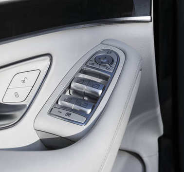 Car white leather interior details of door handle with windows controls and adjustments. Car window controls of modern car.