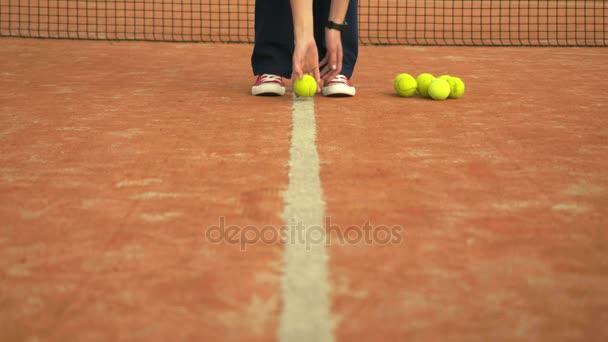 Tenisové míčky na kurtu s net v pozadí