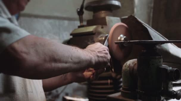 Handwerker schleift Messer in der Werkstatt