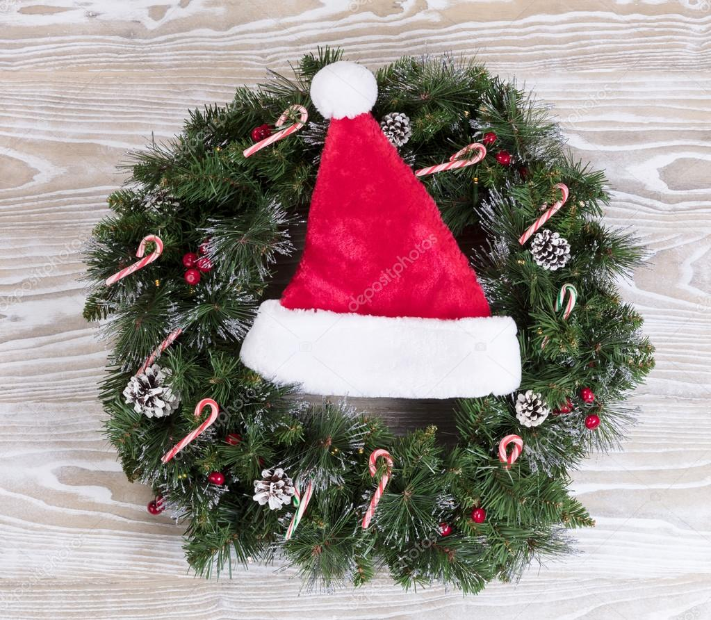 Kerst krans en kerst pet met verlichting en snoep stokken op wh ...