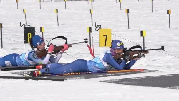 Dvě ruské sportovkyně biatletky míří, střílejí z pušky a nabíjejí se v náchylné poloze. Biatlet střelnice během juniorských biatlonových soutěží East Cup