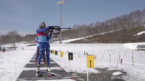 Sportovkyně biatletka Vlada Shishkina míří, puška střílí ve stoje na střelnici. Soutěže juniorského biatlonu východně od poháru