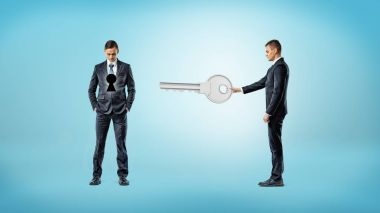 A businessman holds out a giant key in the direction of another man who has a dark keyhole on his torso.
